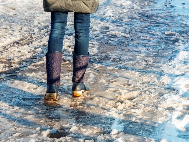 Chão com crosta de gelo, uma mulher caminhando em uma rua escorregadia, clima de primavera. condições geladas