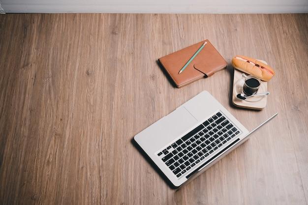 Chão de madeira com computador portátil