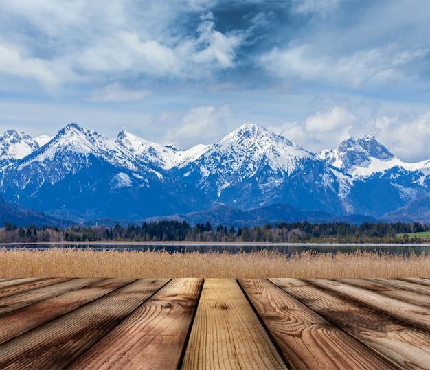 Chão de pranchas de madeira com paisagem dos alpes da baviera
