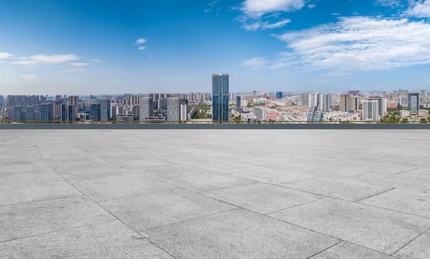 Chão de tijolos vazio com fundo do horizonte da cidade