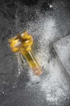 Chão de trigo fresco derramado na placa de madeira com um copo de óleo