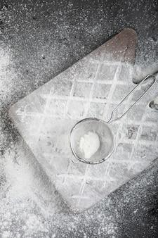 Chão de trigo fresco derramado na placa de madeira na superfície preta