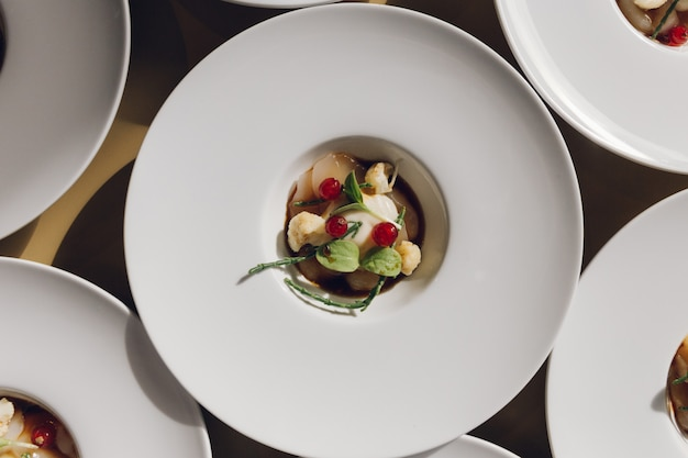 Chapa branca cheia de um delicioso prato com legumes na mesa