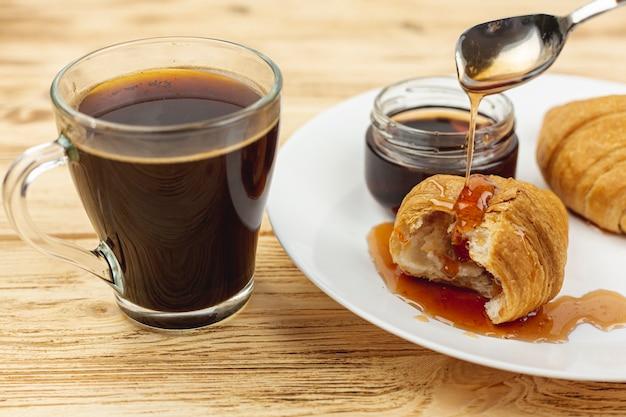 Chapa branca com mel e croissants e uma xícara de café