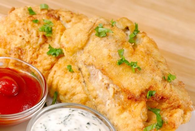 Chapa branca com peixe frito, maionese e ketchup na mesa de madeira