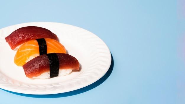Chapa branca com sushi de atum e salmão sobre um fundo azul
