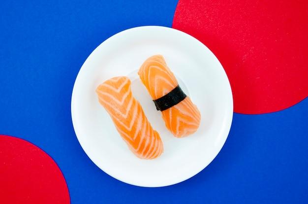 Chapa branca com sushi de salmão em um fundo azul e vermelho