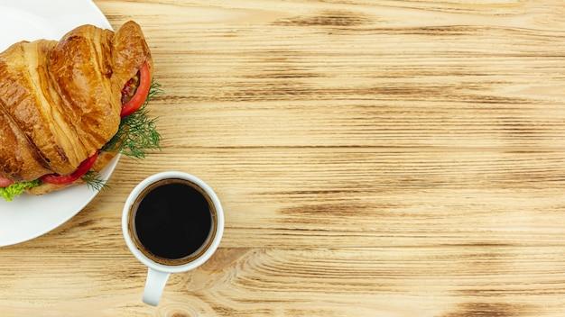Chapa branca com um sanduíche e uma xícara de café