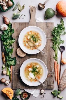 Chapa branca de sopa de legumes caseira em fundo de madeira