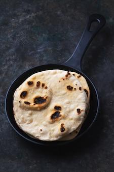 Chapati de pão sírio indiano tradicional. na frigideira de ferro fundido conceito de cozinha caseira fácil. fechar-se. foco seletivo
