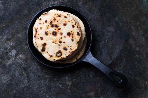 Chapati tradicional indiano de pão achatado em frigideira de ferro fundido. conceito de cozinha caseira fácil. vista do topo. lay flat.