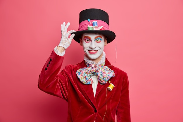 Chapeleiro maluco positivo mantém sorrisos de chapéu na mão feliz participa de vestidos de carnaval para poses de festa de halloween contra uma parede rosada