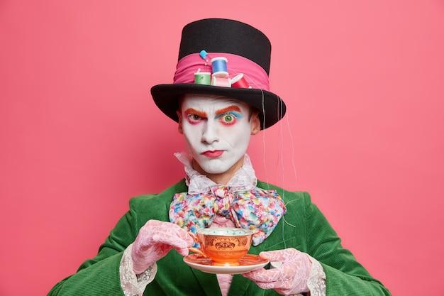 Chapeleiro sério do país das maravilhas bebe chá na festa parece rigoroso na câmera e usa traje especial pronto para o carnaval de halloween isolado sobre a parede rosa
