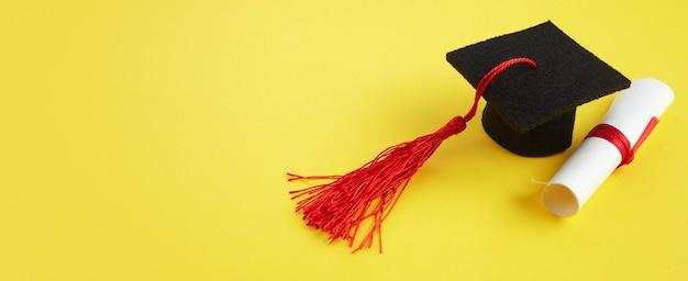 Chapéu acadêmico com diploma em tema de formatura de fundo amarelo