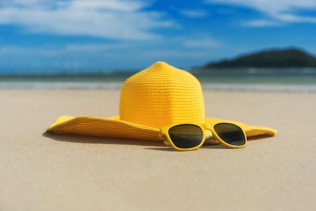 Chapéu amarelo com óculos de sol na areia