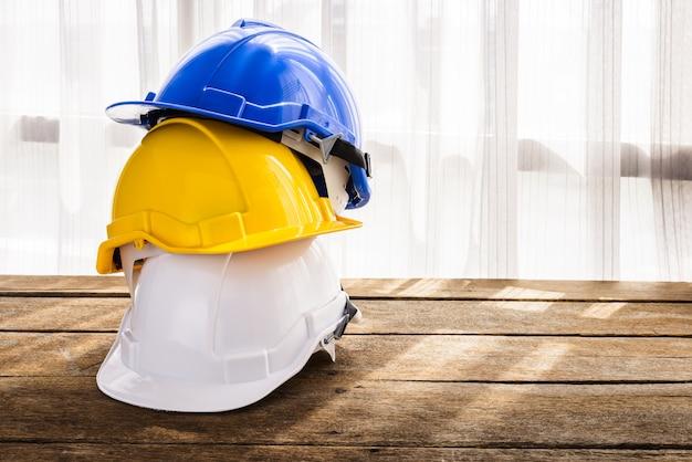 Chapéu azul, amarelo, branco duro da construção do capacete de segurança para o projeto da segurança do trabalhador como o coordenador ou o trabalhador