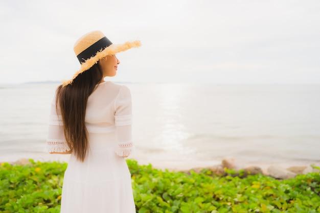 Chapéu bonito asiático do desgaste de mulher do retrato com lazer feliz do sorriso na praia e no mar em férias do feriado