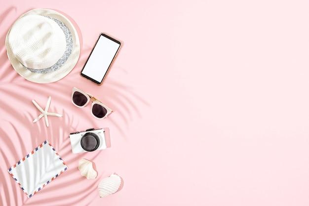 Chapéu branco de verão com acessórios em fundo rosa e sombra de folhas de palmeira