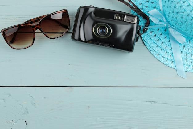Chapéu, câmera e óculos de sol do conceito de viagens sobre um fundo azul de madeira. vista do topo. espaço para texto