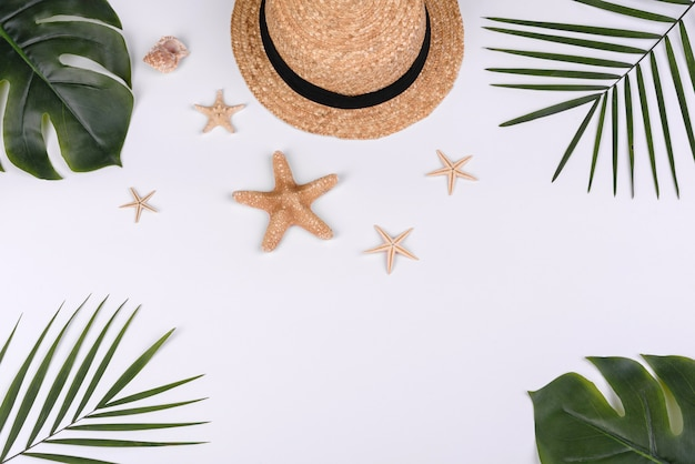 Chapéu com conchas e estrelas do mar em um fundo branco. fundo de verão