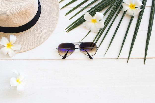 Chapéu com óculos de sol da mulher estilo de vida relaxar frangipani verão e flor, folha de coco em branco de madeira