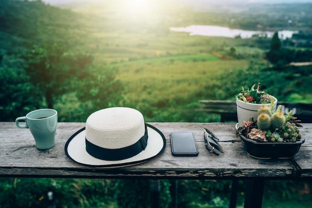 Chapéu, copo, óculos escuros e smartphone em uma tabela