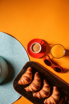 Chapéu, croissant de óculos de sol com uma xícara de café e um copo de suco de laranja em uma mesa amarela ao sol