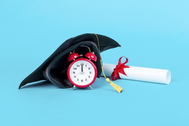 Chapéu da formatura no relógio vermelho perto do diploma, imagem em um fundo azul, hora da formatura do conceito