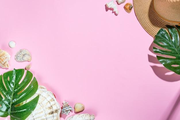 Chapéu de acessórios de praia, folhas de palmeira, chapéu de praia de estrela do mar e concha do mar em fundo de papel rosa