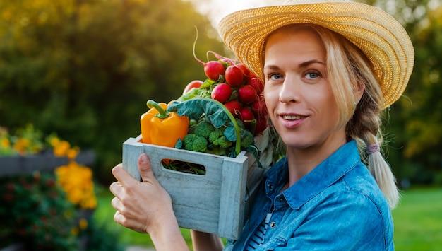 Chapéu de agricultor jovem bonita com caixa de legumes ecológicos frescos