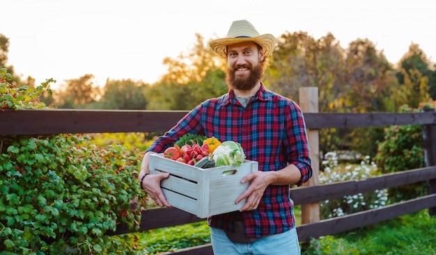 Chapéu de agricultor masculino jovem barbudo com jardim de legumes ecológicos frescos de caixa