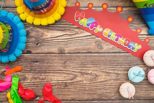 Chapéu de aniversário; coroa; balões e macarons em fundo de madeira