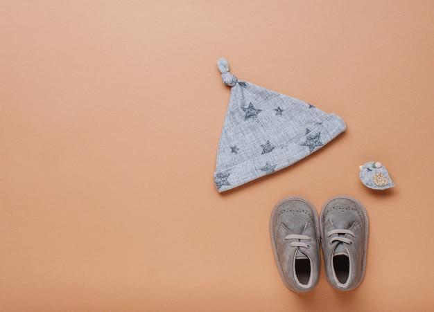 Chapéu de bebê e sapatos em fundo bege com espaço em branco para texto. vista superior, configuração plana.