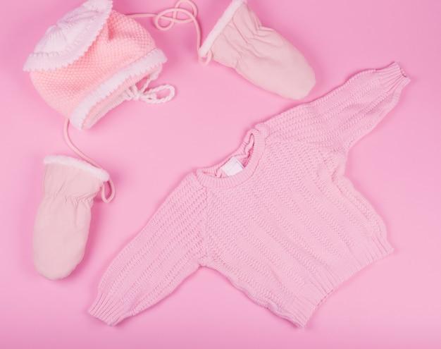 Chapéu de bebê, luvas e suéter de cor rosa