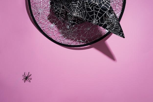 Chapéu de bruxa preta com um padrão de teias de aranha e aranha no fundo rosa