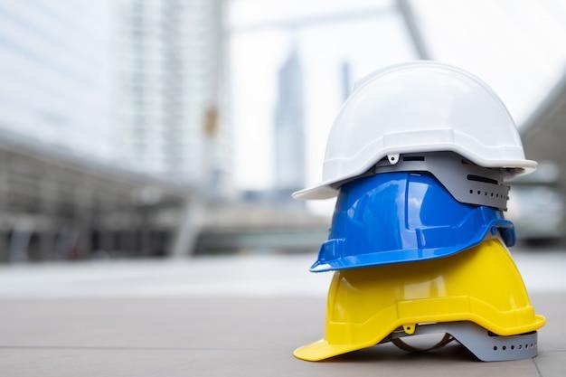 Chapéu de capacete de desgaste de segurança no projeto no canteiro de obras de construção no piso de concreto na cidade.