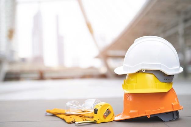 Chapéu de capacete de proteção rígido laranja, amarelo, azul e branco no projeto no canteiro de obras em piso de concreto na cidade