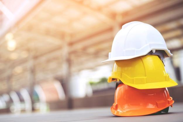 Chapéu de capacete de segurança dura no projeto no canteiro de obras de construção em piso de concreto na cidade.