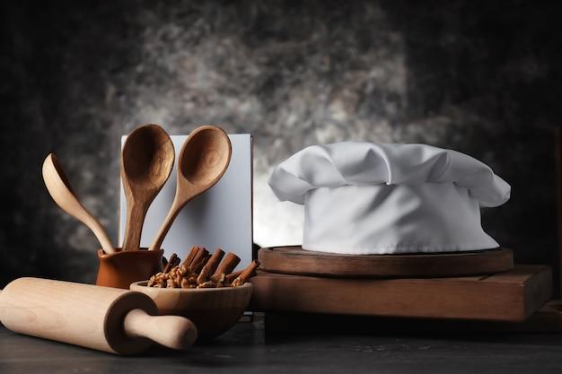 Chapéu de chef com utensílios de cozinha no escuro