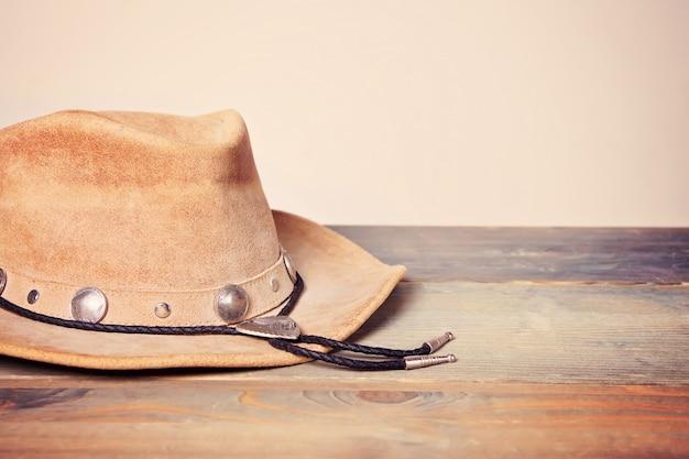 Chapéu de cowboy marrom em uma mesa de madeira