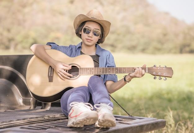Chapéu de desgaste de mulher e tocar violão na pick-up