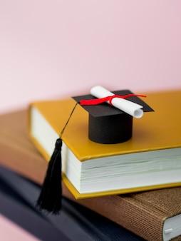 Chapéu de formatura alto ângulo e diploma em livros diferentes