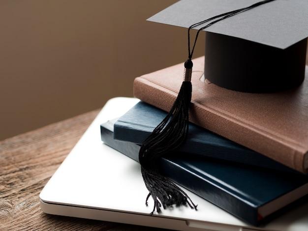 Chapéu de formatura alto ângulo na pilha de livros