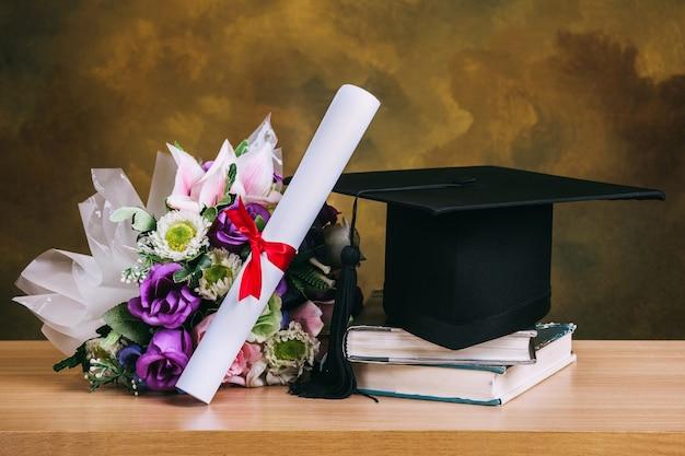 Chapéu de formatura, chapéu com papel de grau e buquê de flores na mesa de madeira.