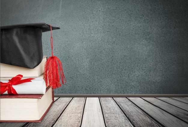 Chapéu de formatura com borla, diploma com fita vermelha