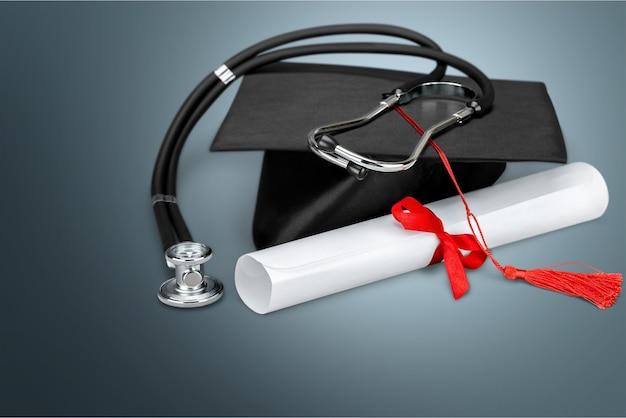 Chapéu de formatura com borla, diploma com vermelho