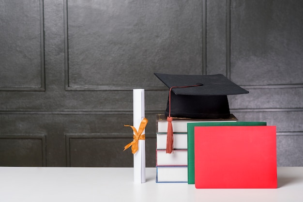 Chapéu de formatura com livros na mesa branca, fundo de educação