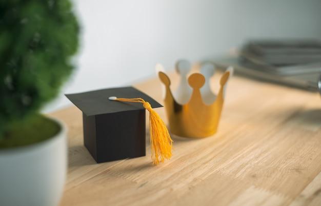 Chapéu de formatura de ofício de papel de construção e coroa de ouro na mesa de madeira