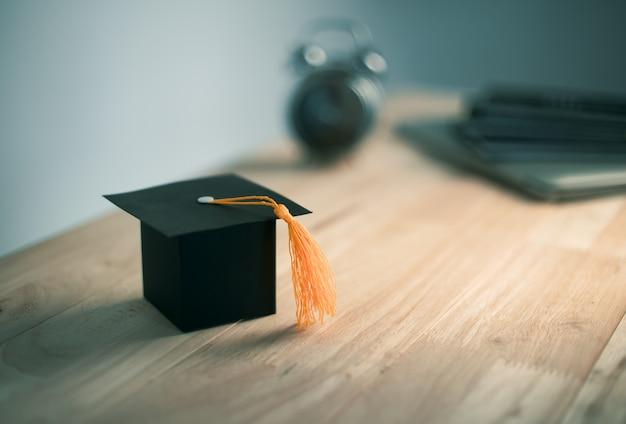 Chapéu de formatura de ofício de papel de construção na mesa de madeira