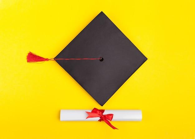 Chapéu de formatura e diploma em fundo amarelo